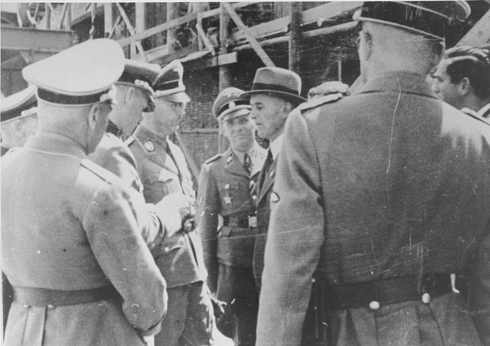 Officials at the Monowitz-Buna building site greet Reichsfuehrer SS Heinrich Himmler and his inspection team.     Among those pictured are Max Faust (wearing the fedora), the head of building operations for IG Farben in Monowitz-Buna; and Heinrich Himmler (third from the left).  Facign the camera (fourth from the left) is Rudolf Hoess, Commandant of Auschwitz.