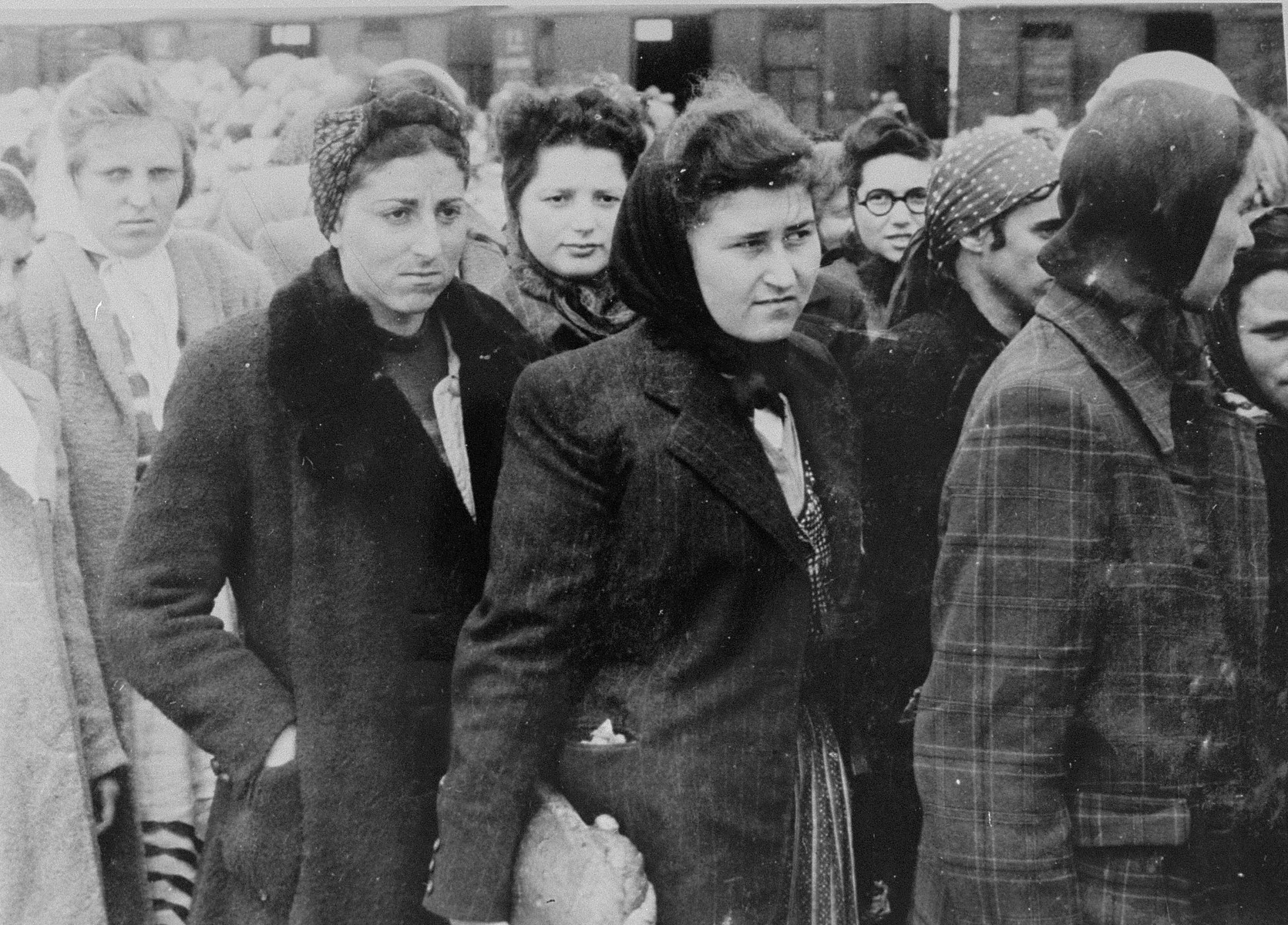 Jewish women from Subcarpathian Rus await selection on the ramp at Auschwitz-Birkenau.  Among those pictured is Chava Maged (first from the left, in the back) from Tecevo. Partially obscured to her right is her younger sister, Esther.  In front of her is Sury Moskovics from Visk. Rochi Falkovics stands in the front row.  Behind her on the left is Sury Fuks and her sister (wearing glasses).