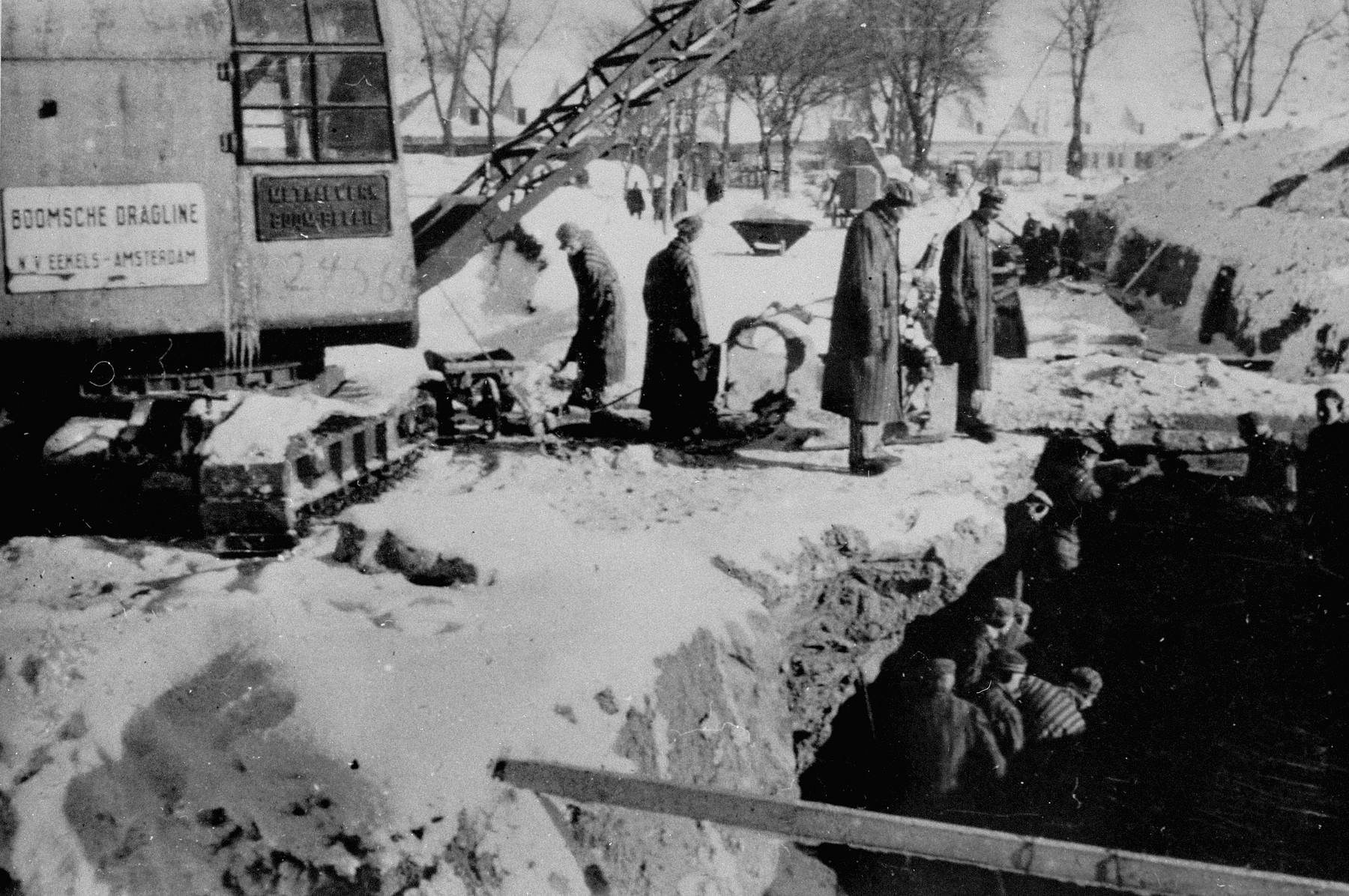 Prisoners at forced labor digging a drainage or sewerage trench in Auschwitz.
