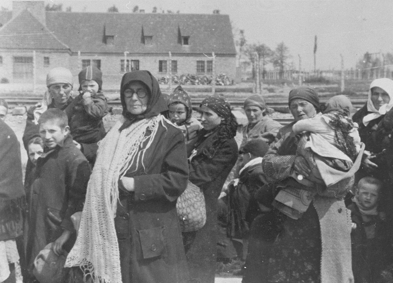 Jewish women and children from Subcarpathian Rus who have been selected for death at Auschwitz-Birkenau, walk toward the gas chambers.  The building in the background is crematorium III.   Those pictured include Iboja Hoffman of Bodrogkeresztur, her aunt Lena Egri, Ruth Hoffman (Iboja's sister), Malwin Hoffman (Iboja and Ruth's mother), Piroska Szaz of Tokaj (Lena and Malwin's sister), Piroska's daughter and Karcsi Szaz (Piroska's son).