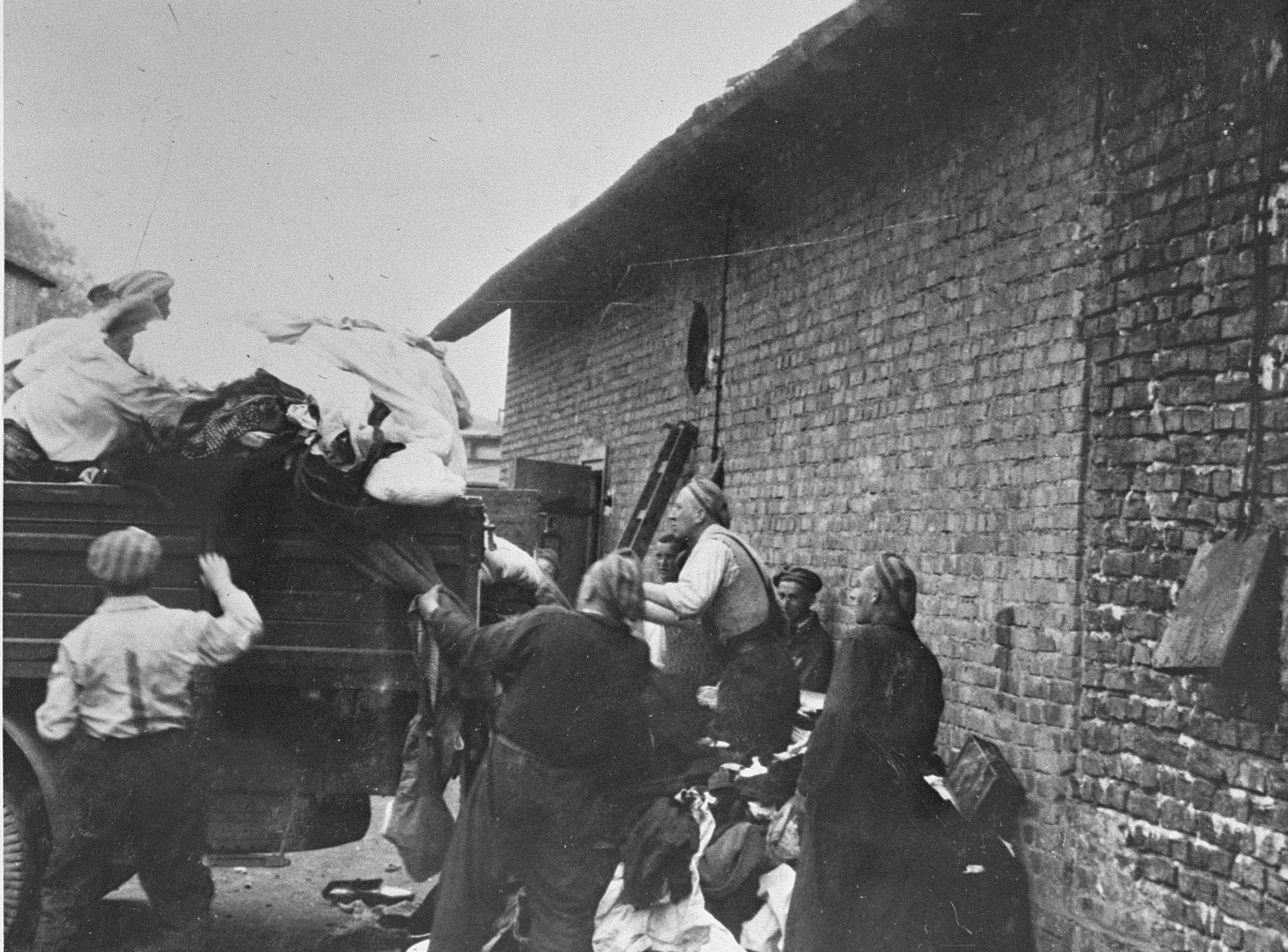 "Prisoners in the Aufräumungskommando (order commandos) unload the confiscated property of a transport of Jews from Subcarpathian Rus at a warehouse in Auschwitz-Birkenau.  The camp prisoners came to refer to the looted property as ""Kanada,"" associating it with the riches symbolized by Kanada.  The members of this commando were almost exclusively Jews.  ""Kanada"" storage facilities occupied several dozen barracks and other buildings around the camp.  The looted property was funneled from Auschwitz through an extensive distribution network that served many individuals and various economic branches of the Third Reich.  Standing from left to right are Simon Bobker, Alexander Wertheimer. Chaim Laufer and Miso Vogel."