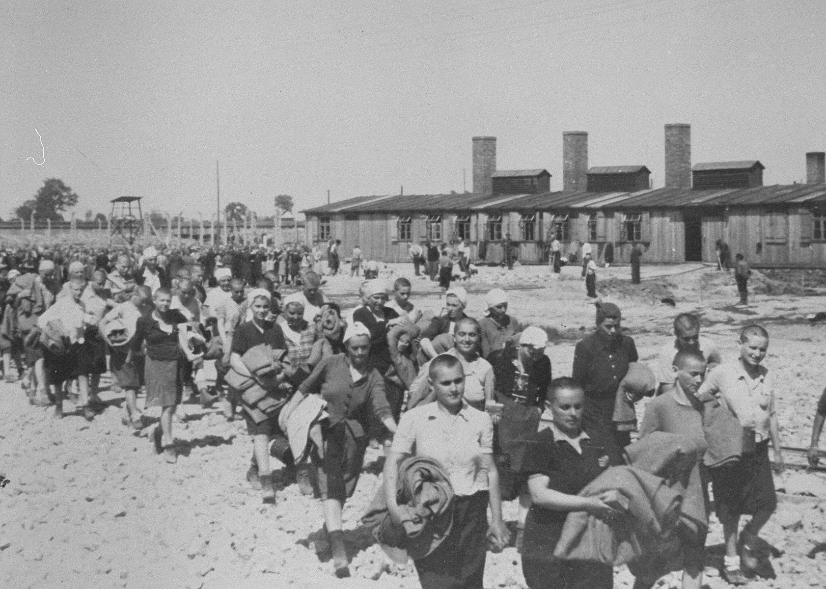 Jewish women from Subcarpathian Rus and Czechoslovakia who have been selected for forced labor at Auschwitz-Birkenau, march toward their barracks carrying bed rolls after disinfection and headshaving.  Ilse Drexler Bauer (later Maier) is on the left column fourth from the front in a dark dress and white scarf.  Her cousin Margit Novakova is directly in front of her in a grey dress and white hat.  According to Ilse Maier this was a mixed Czech Hungarian work detail.