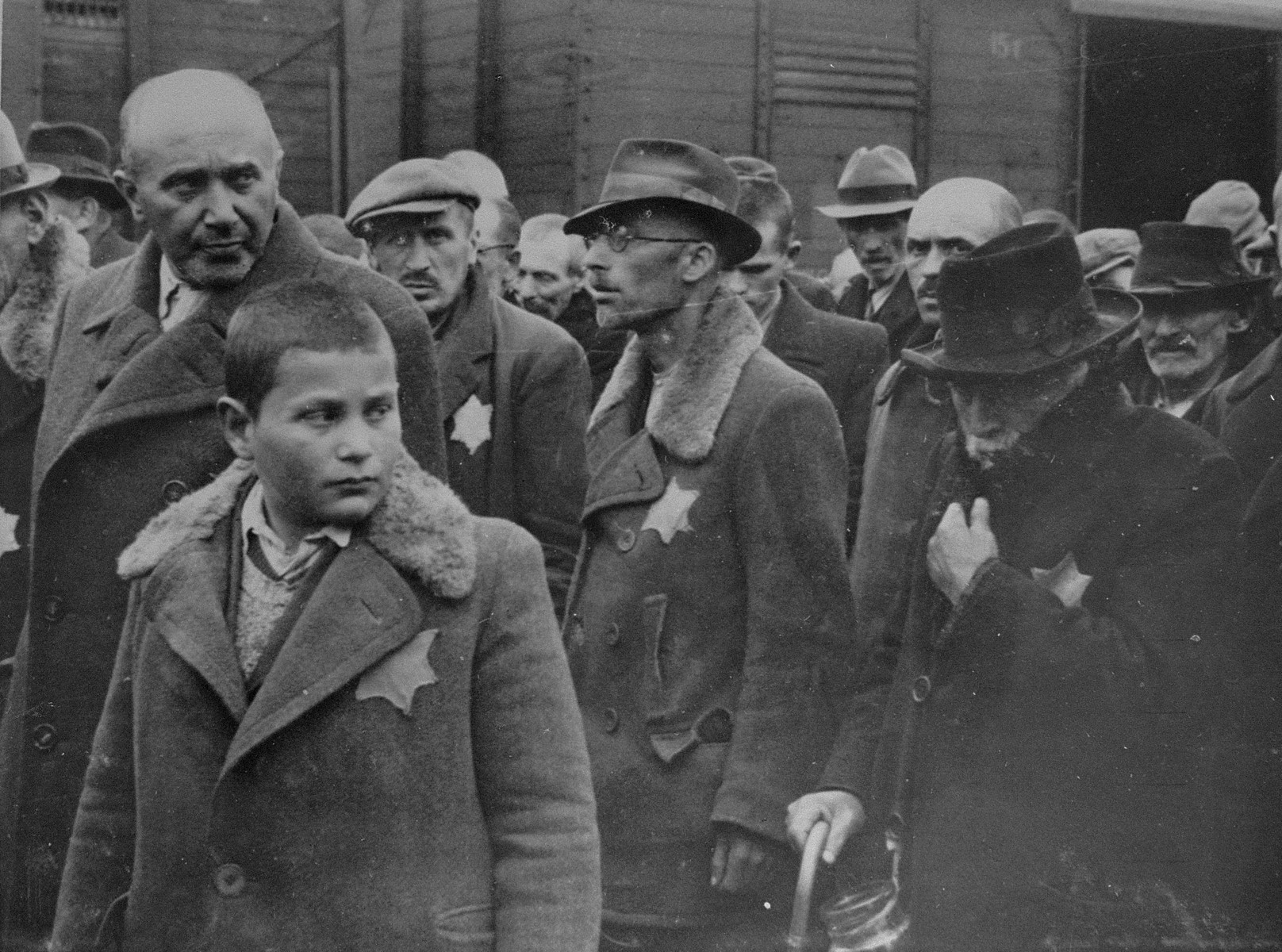Jewish men and boys from Subcarpathian Rus await selection on the ramp at Auschwitz-Birkenau.  The man in the center wearing glasses is Sigmund Bruck, a mechanical engineer from Tab.  Bruck was denounced as a communist, arrested and deported to Nagy Kamizsa.  He was eventually sent to Auschwitz-Birkenau and then to Gleiwitz, where he was killed by a guard during an escape attempt.  To his left is Mr. Smilazick and his son.