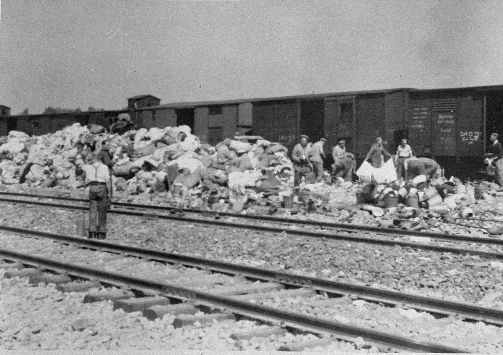 "Prisoners in the Aufräumungskommando (order commandos) sort through a mound of personal belongings confiscated from the arriving transport of Jews from Subcarpathian Rus.    Among those working near the train is Chaim Rephael from Salonika.  The camp prisoners came to refer to the looted property as ""Canada,"" associating it with the riches symbolized by Canada.  The members of this commando were almost exclusively Jews.  ""Canada"" storage facilities occupied several dozen barracks and other buildings around the camp.  The looted property was funneled from Auschwitz through an extensive distribution network that served many individuals and various economic branches of the Third Reich."