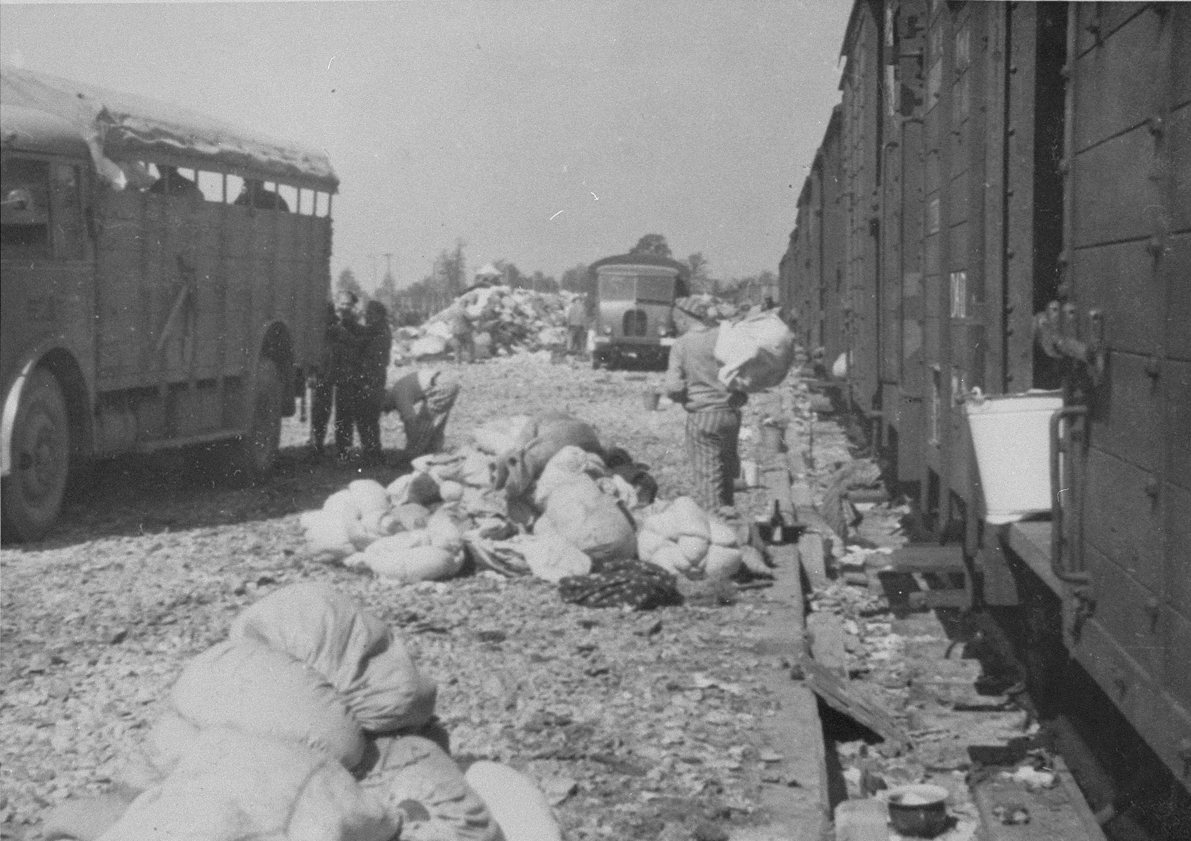 "Prisoners in the Aufräumungskommando (order commandos) sort through a mound of personal belongings confiscated from the arriving transport of Jews from Subcarpathian Rus.    The camp prisoners came to refer to the looted property as ""Canada,"" associating it with the riches symbolized by Canada.  The members of this commando were almost exclusively Jews.  ""Canada"" storage facilities occupied several dozen barracks and other buildings around the camp.  The looted property was funneled from Auschwitz through an extensive distribution network that served many individuals and various economic branches of the Third Reich."