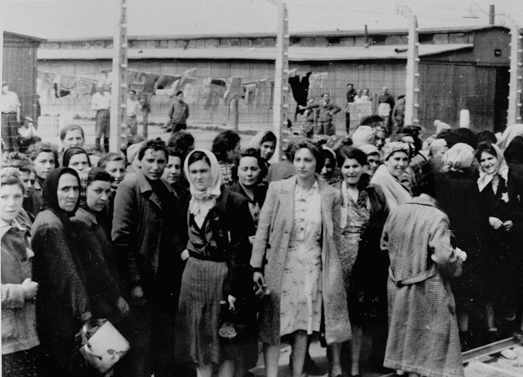 Jewish women from Subcarpathian Rus who have been selected for forced labor at Auschwitz-Birkenau, wait to be taken to another section of the camp.   Behind the fence is block BIId where 20,000 men were imprisoned.   Among those pictured are Gizi Krousz Kauf of Szeged, Rozsi Egri Swartz, Zseni Stern of Bodrogkeresztur, Ester Erzsebet Egri Deutsch (Rozsi's niece) of Bodrogkeresztur, Freda Egri Salomon (Ester's sister), Aranka Stern (Zseni's niece) and Etu Szumet of Bodrogkeresztur.