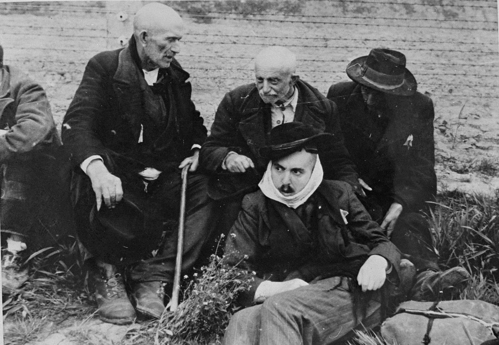 Elderly Jewish men from Subcarpathian Rus sit on the grass in Auschwitz-Birkenau prior to being sent to the gas chambers.  One of the men wears a scarf to cover his shaven face.