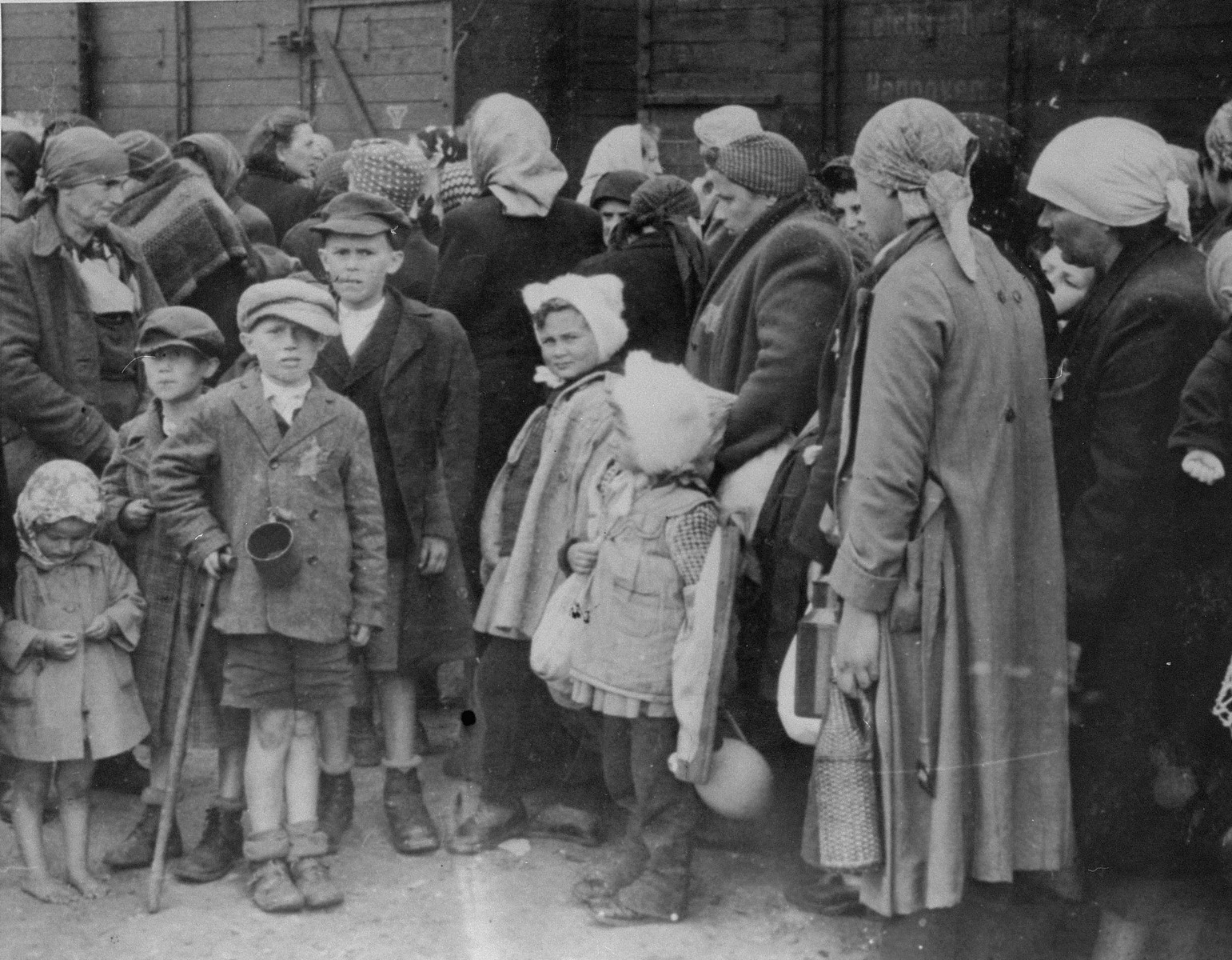Jewish women and children from Subcarpathian Rus await selection on the ramp at Auschwitz-Birkenau.  Lili Jacob's has identified aunt Tauba with her four children.  The woman in the center with the two girls wearing rabbit fur hats have been identified as either Bozsi Iskovics Engel (b. 1904) from Beregszasz with her two daughters Agota Engel (b. 1933) and Judith Engel (b. 1936) or Breine Slomovics with her two daughters.