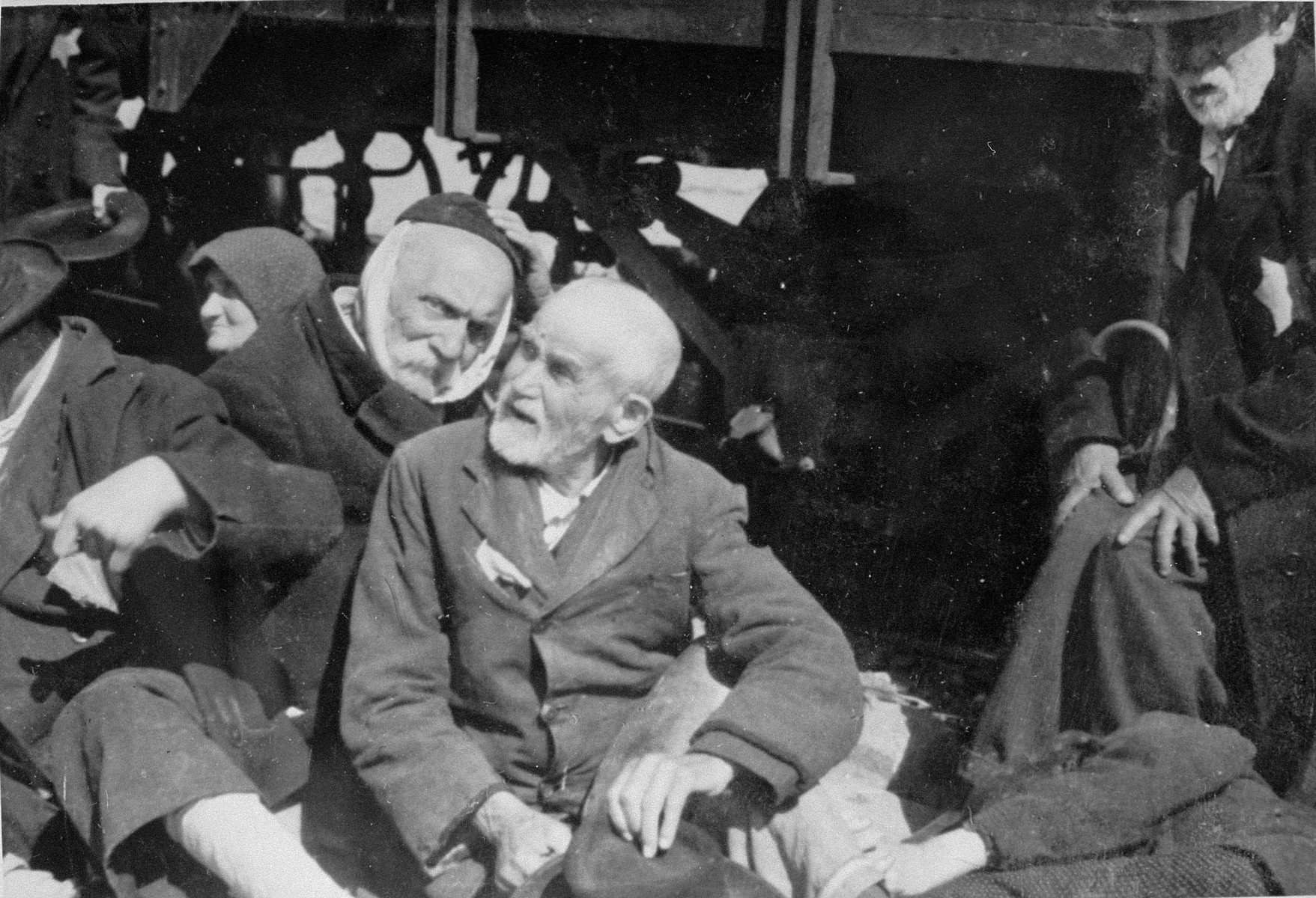 Elderly Jewish men from Subcarpathian Rus sit next to a railcar in Auschwitz-Birkenau prior to being sent to the gas chambers.   One of the men wears a scarf to cover his shaven face.  The man on the far right is Lili Jacob's paternal grandfather.