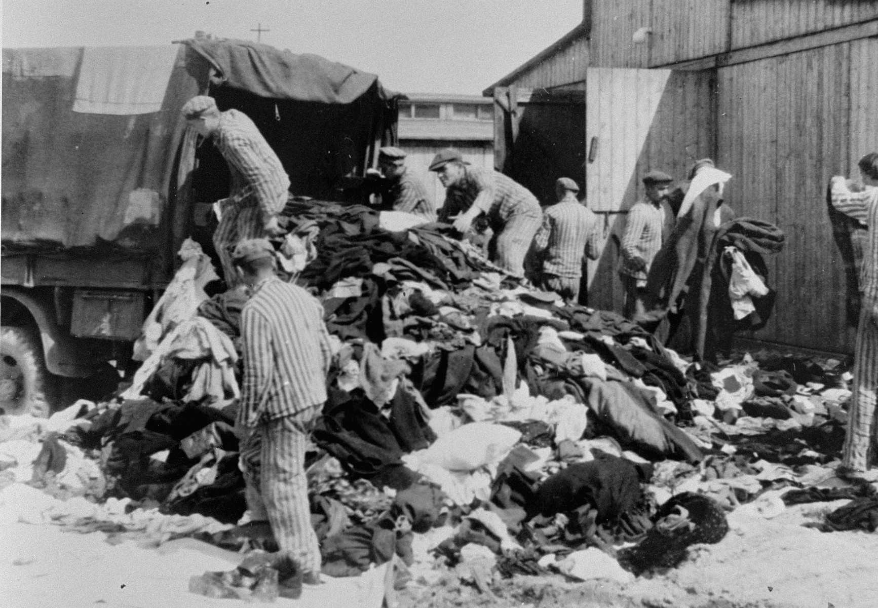"Prisoners in the Aufräumungskommando (order commandos) unload the confiscated property of a transport of Jews from Subcarpathian Rus at a warehouse in Auschwitz-Birkenau.  The camp prisoners came to refer to the looted property as ""Kanada,"" associating it with the riches symbolized by Kanada.  The members of this commando were almost exclusively Jews.  ""Kanada"" storage facilities occupied several dozen barracks and other buildings around the camp.  The looted property was funneled from Auschwitz through an extensive distribution network that served many individuals and various economic branches of the Third Reich."