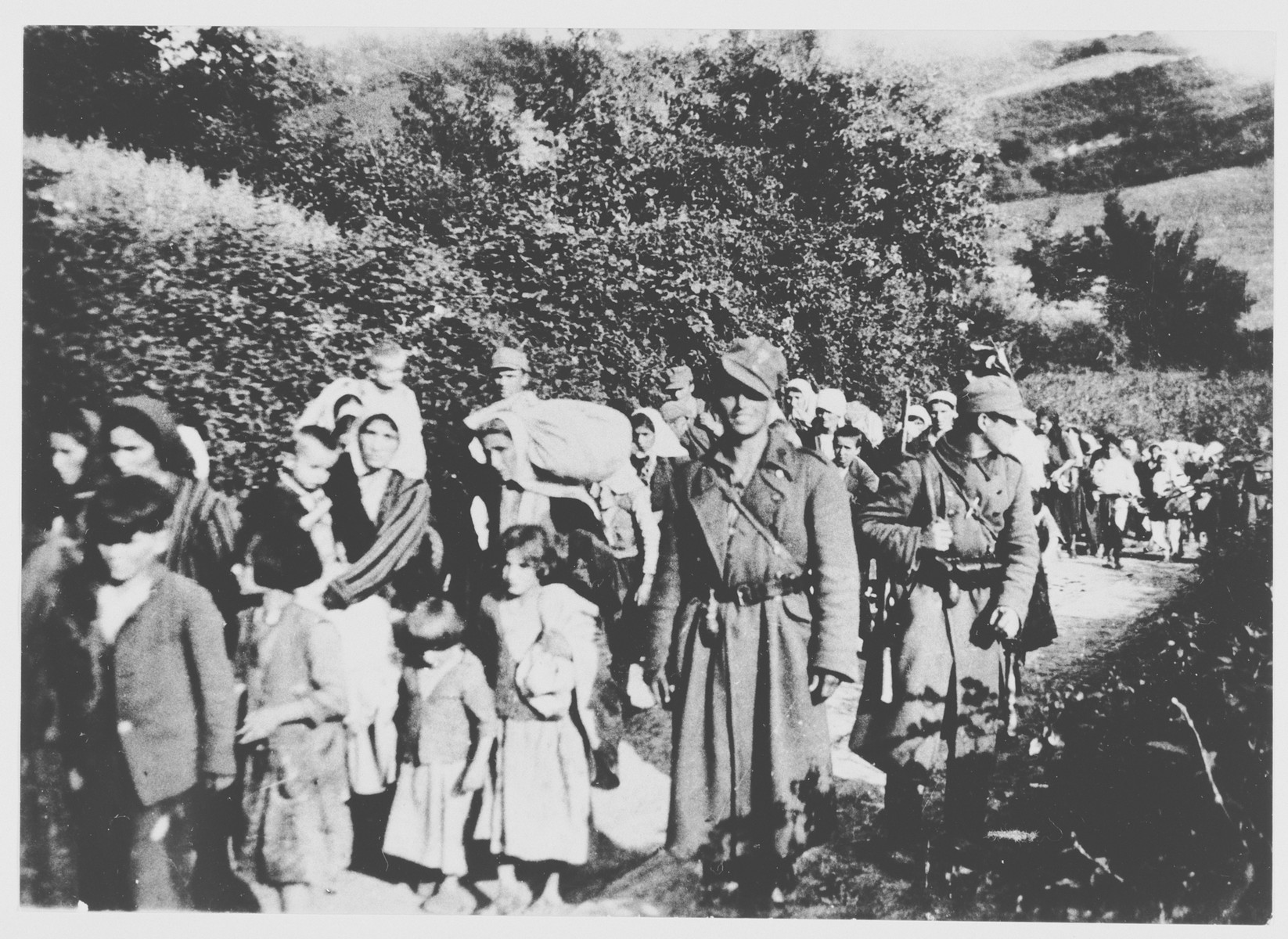 Yugoslav women and children are escorted by Ustasa militiamen to the Jasenovac concentration camp.