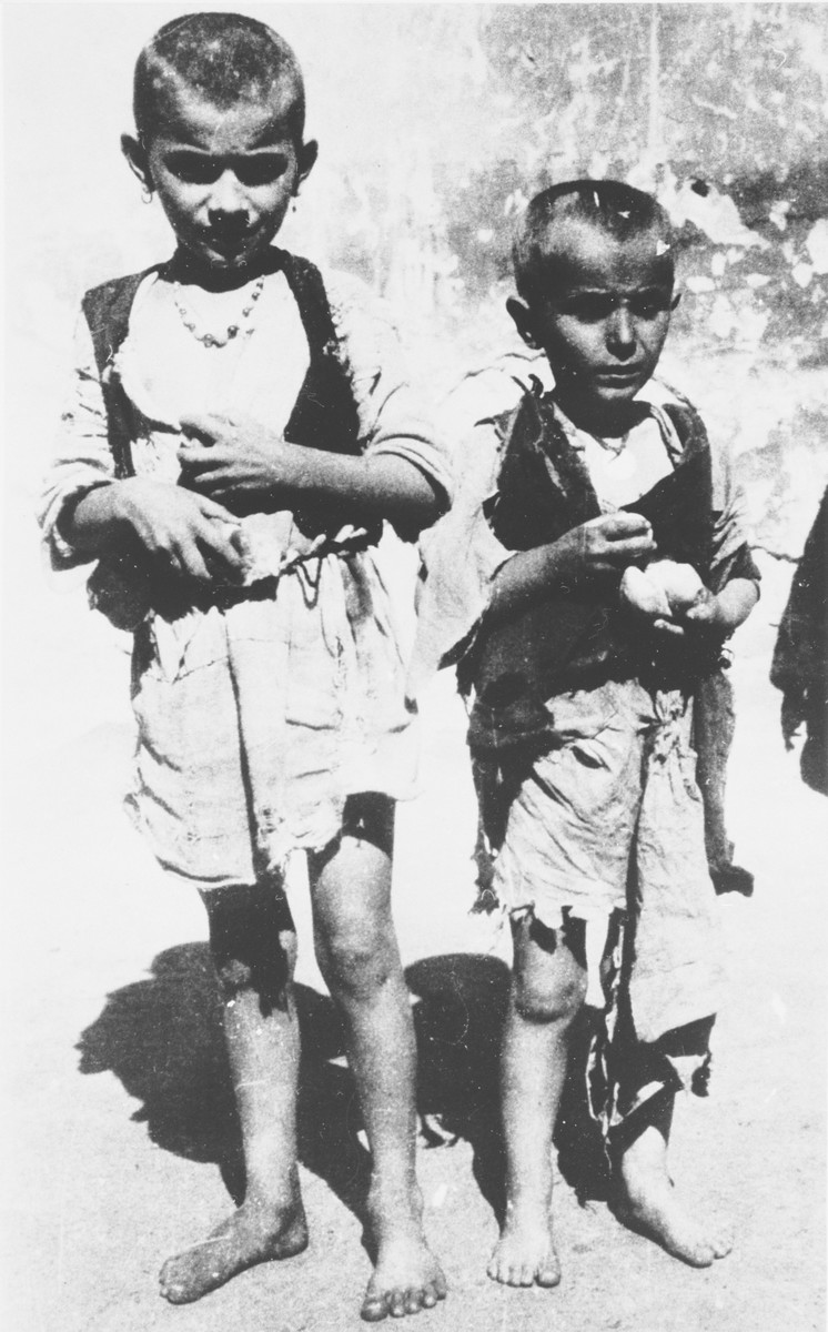Two barefoot, emaciated children pose outside holding a bit of food at the Jastrebarsko concentration camp.