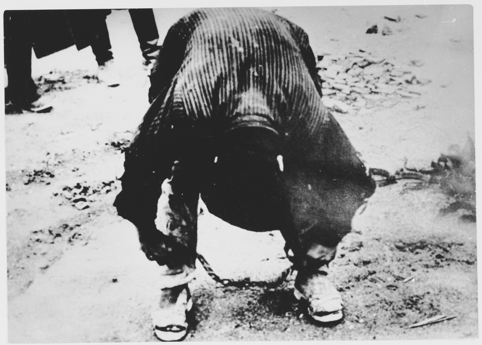 A male inmate of the Stara Gradiska concentration camp bends over to adjust his leg irons.  The photograph was taken during an official visit of a German commission to the concentration camp in the summer of 1942.