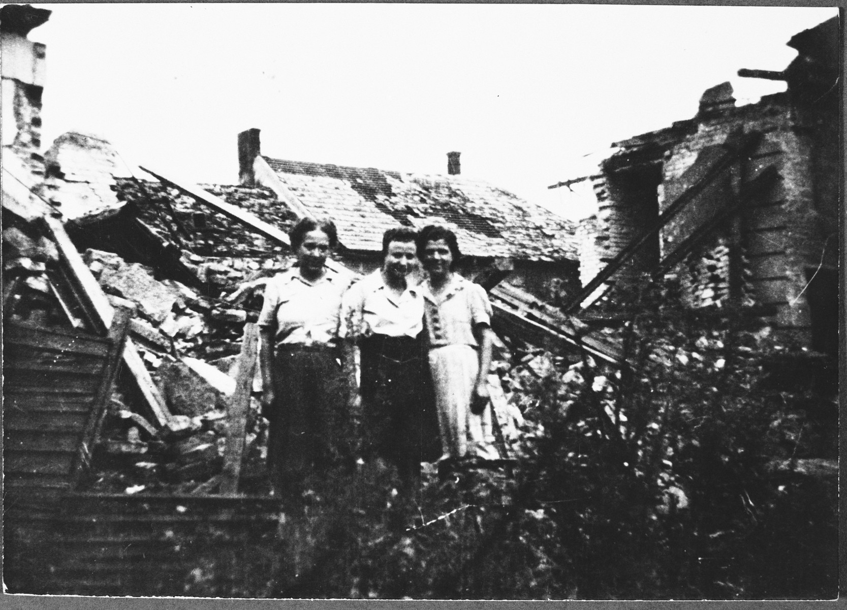 Italian survivors of Theresienstadt stand next to some destroyed buildings on their way home to Italy.  Anna Cassuto is on the left.  Her friend, Amalia Navaro, is on the right.