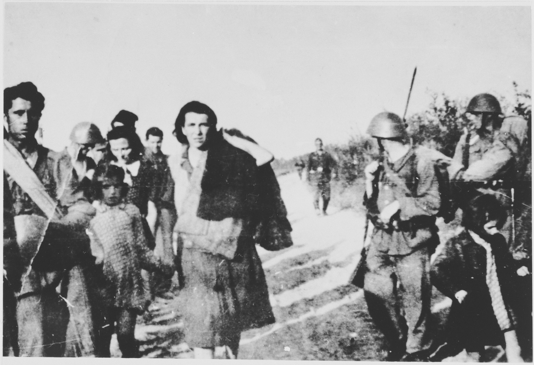 Soldiers lead a group of Serbian villagers from the Kozara region who are being deported to Croatian concentration camps.