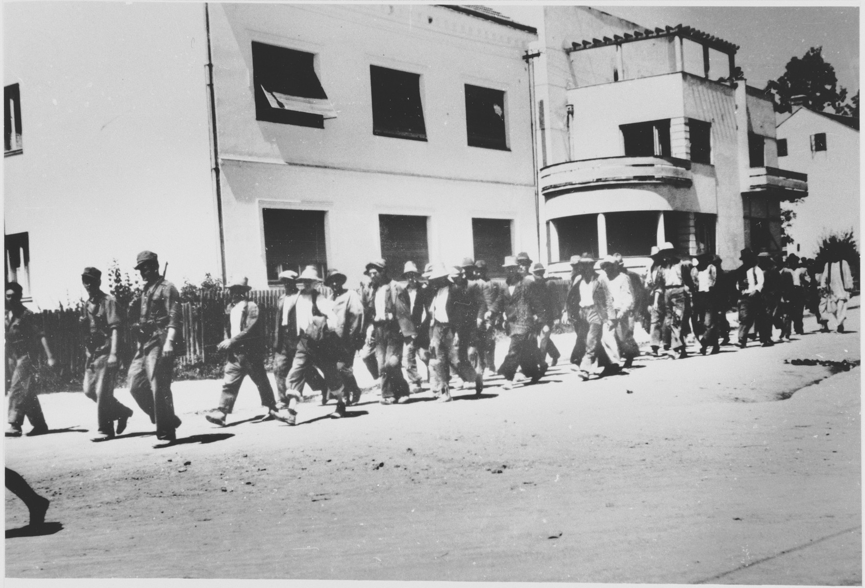 A group of men who have been rounded-up for deportation, are marched out of town [probably by members of the Ustasa militia].