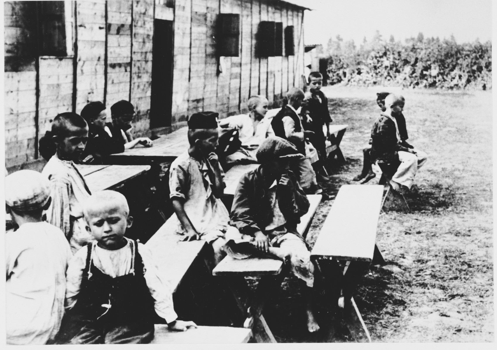 Children sit on benches outside a barracks in the Gornja Rijeka concentration camp.