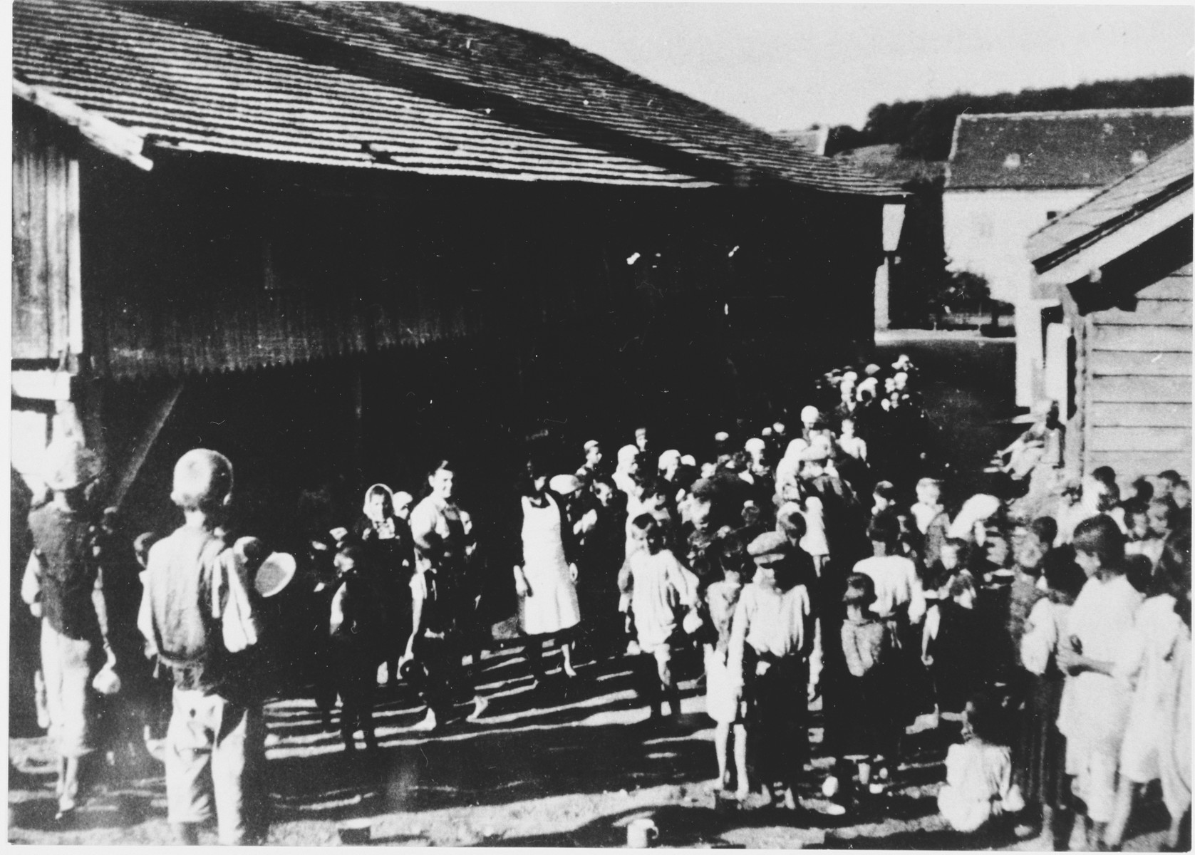 A large group of children are assembled outside in the Gornja Rijeka concentration camp.