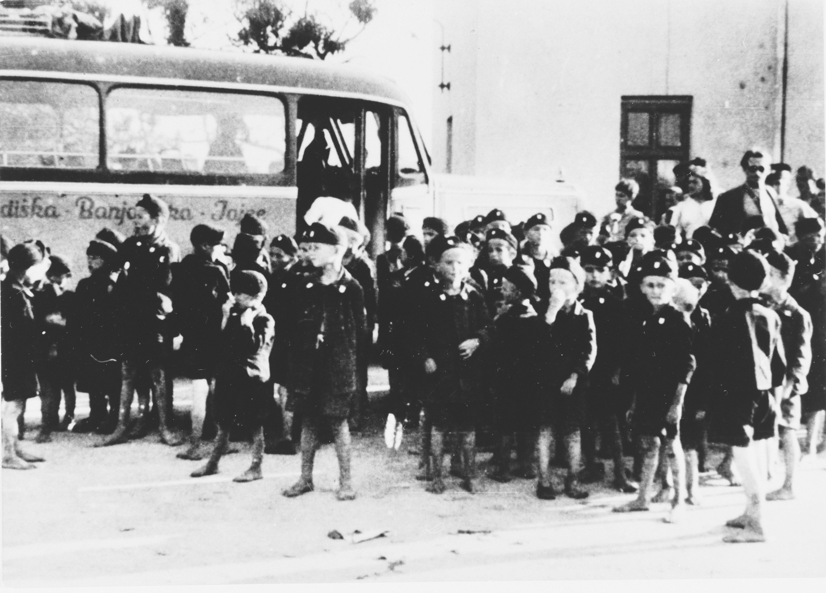 A group of young Serbian children from the Kozara region who are dressed in Ustasa uniform, are assembled next to a bus in the Stara Gradiska concentration camp.  The children were called Lubruric's Little Serbs after Maks Lubruric, the commandant of the Jasenovac concentration camp.  Dressing the imprisoned children in Ustasa uniforms was part of the Croatian regime's effort to reeducate the Serbian boys from the Kozara region.