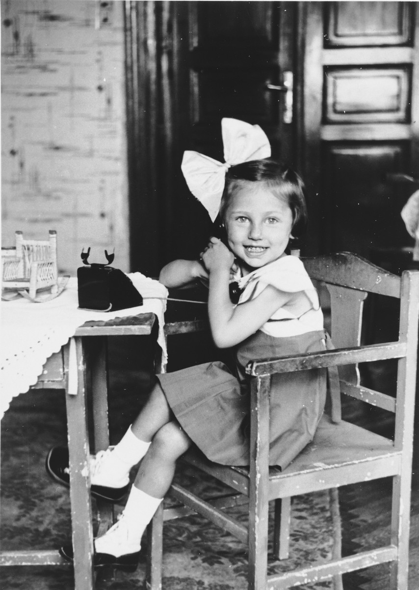 A young Jewish girl sits at a table talking on a toy telephone.  Pictured is Judit Schichtanz.
