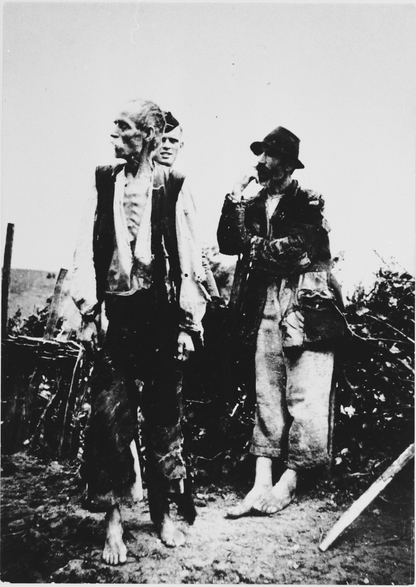 A soldier stands behind two barefoot men.  [Possibly a member of the Ustasha militia guarding two Serbs or Gypsies during a round-up.]