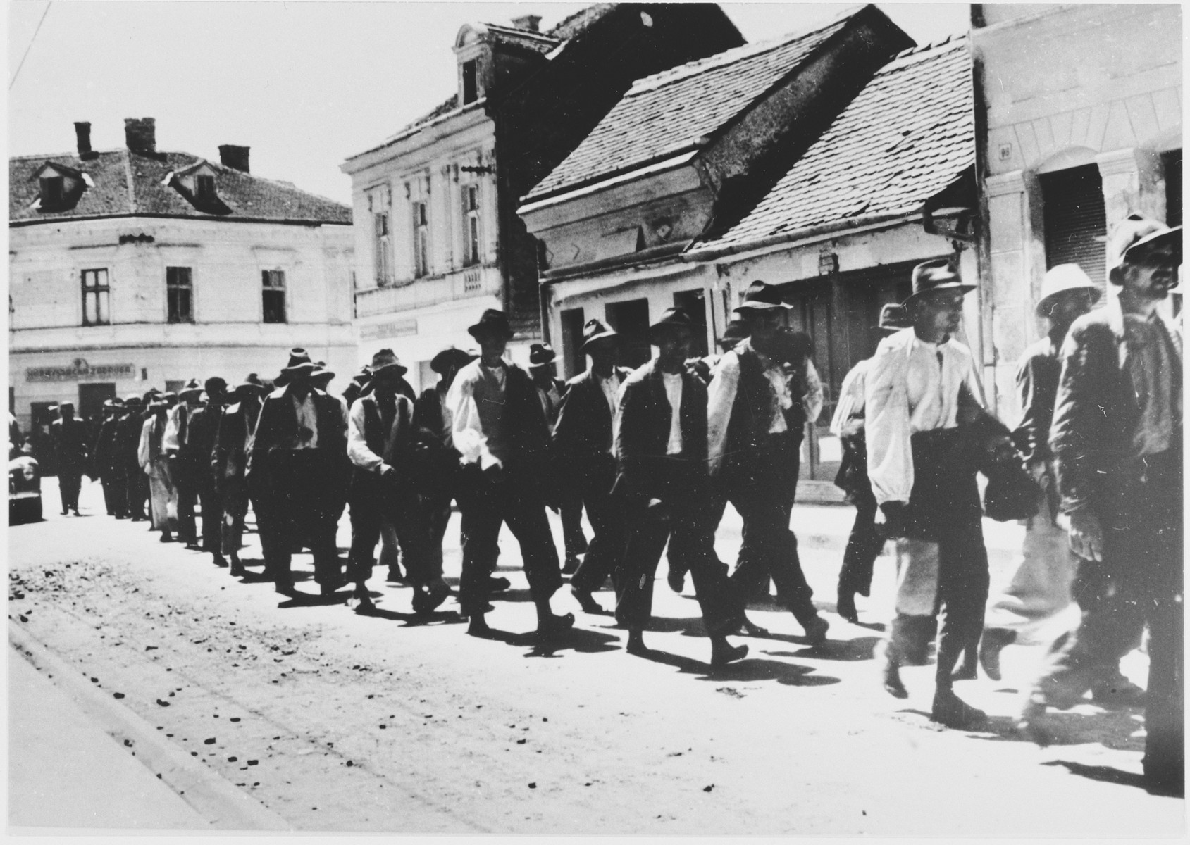 [Probably Serbian villagers from the Kozara region who have been rounded-up for deportation, marching in a column through the streets of a town.]