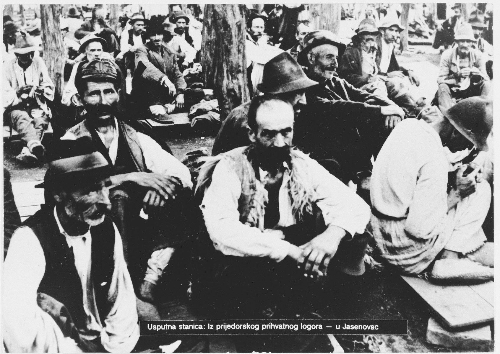 Serbian villagers from the Kozara region who have been rounded-up for deportation, wait in a transit camp in Prijedor for transport to the Jasenovac concentration camp.]