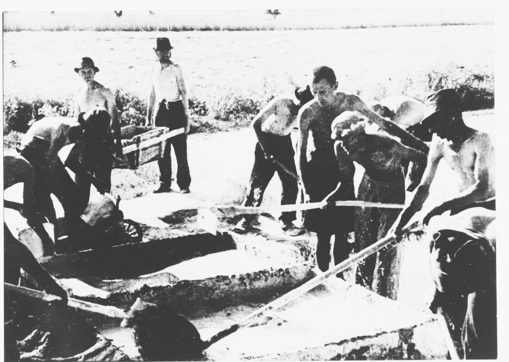 "Prisoners at forced labor in the Jasenovac III concentration camp brickyard mixing lime in large troughs.  The photo was displayed in the exhibit, ""One Year of Work in Transit Camps,"" mounted at the Zagreb fair grounds in the fall of 1942."