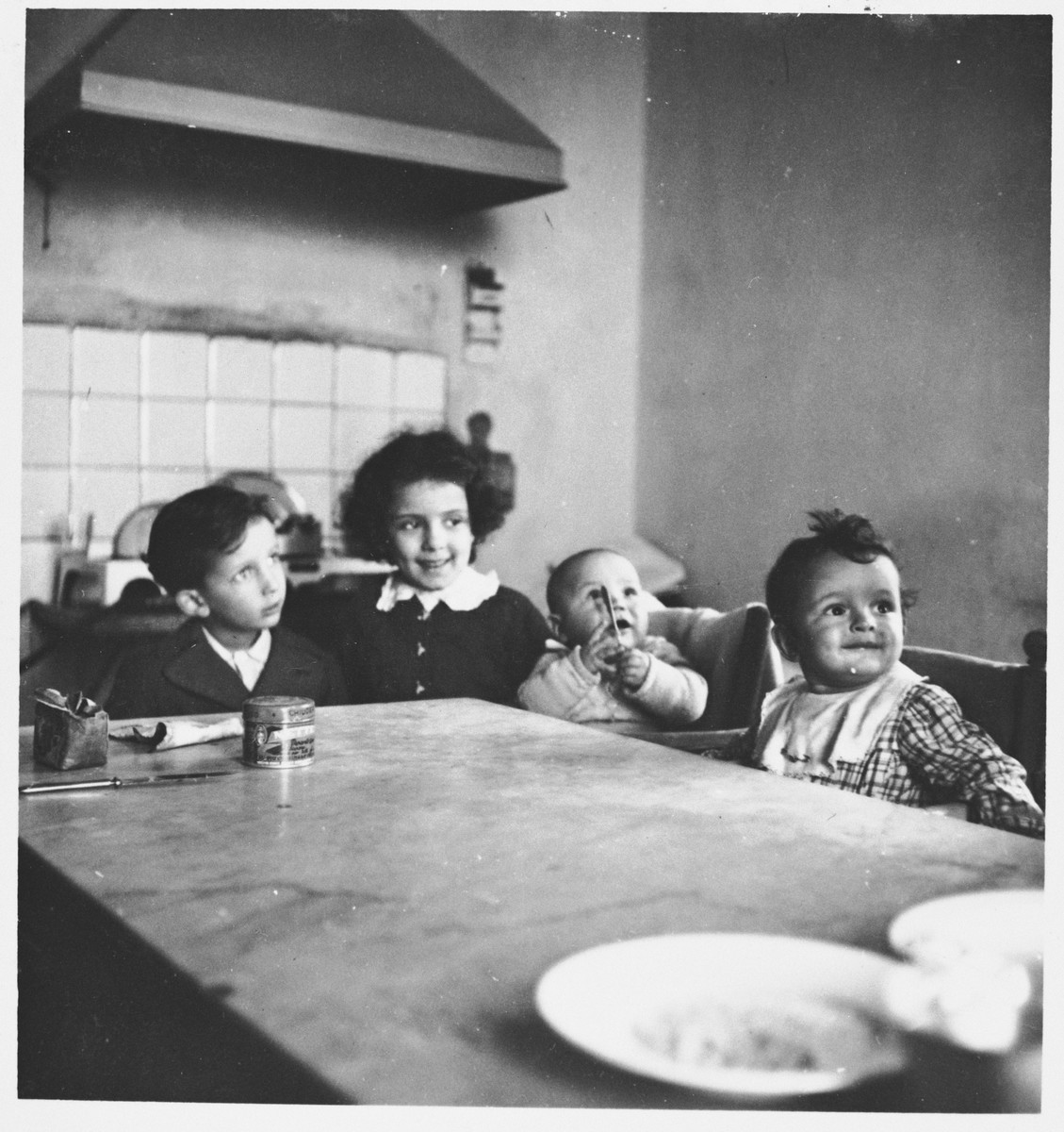 The Cassuto children sit around a kitchen table.  Pictured are Susanna, David, their cousin Umberto DiGiaccino, and Daniel.