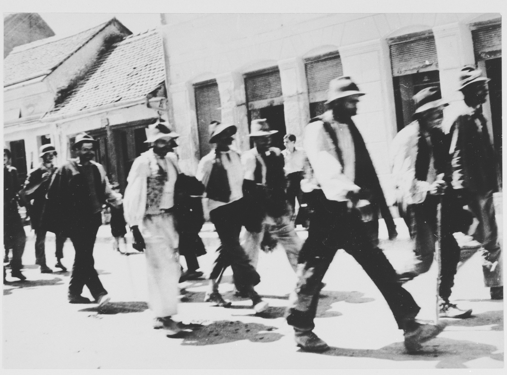 A group of men who have been rounded up for deportation, are marched out of town.