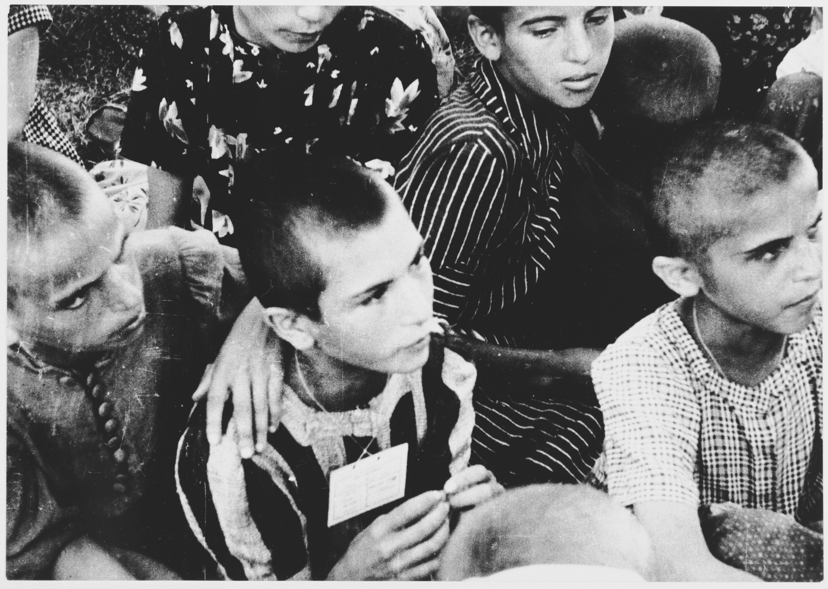 Children with shaven heads and tags around their necks wait to be transferred from the Stara Gradiska concentration camp to Zagreb.