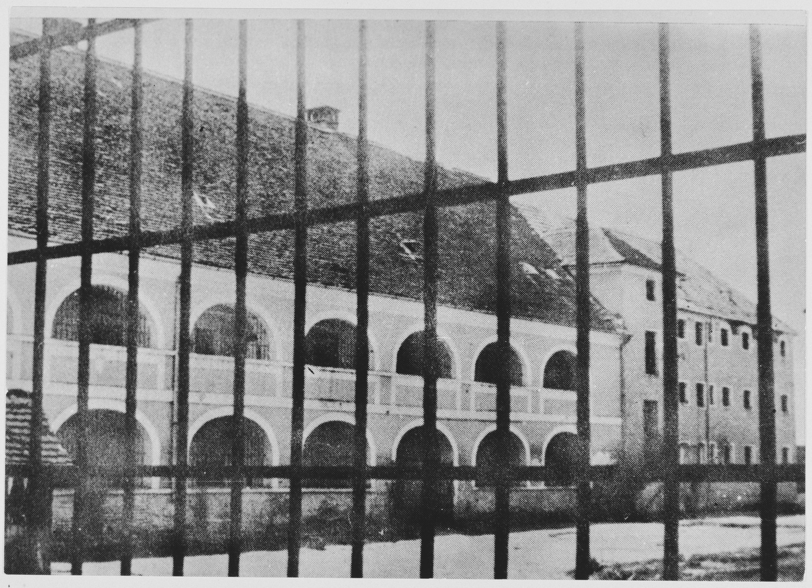 View through a tall fence of prisoner barracks in the men's camp at the Stara Gradiska concentration camp.  At the left are quarters for Jewish and Serbian inmates; at the right, for Croats, Muslims and Catholics.