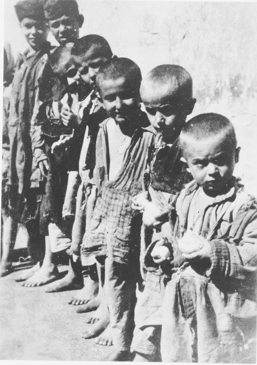 A group of barefoot, emaciated children stand outside in a row at the Jastrebarsko concentration camp.