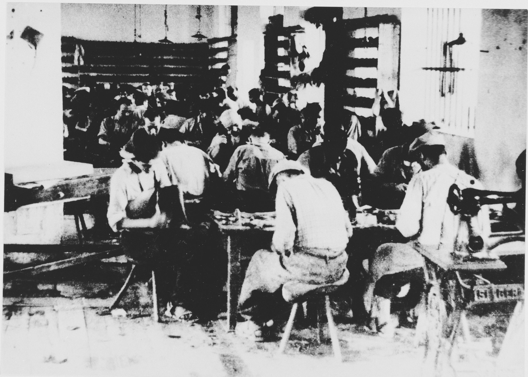 Prisoners labor in a shoe-making workshop in the Jasenovac III concentration camp.  This photograph was used for propagandistic purposes by the Ustasa.