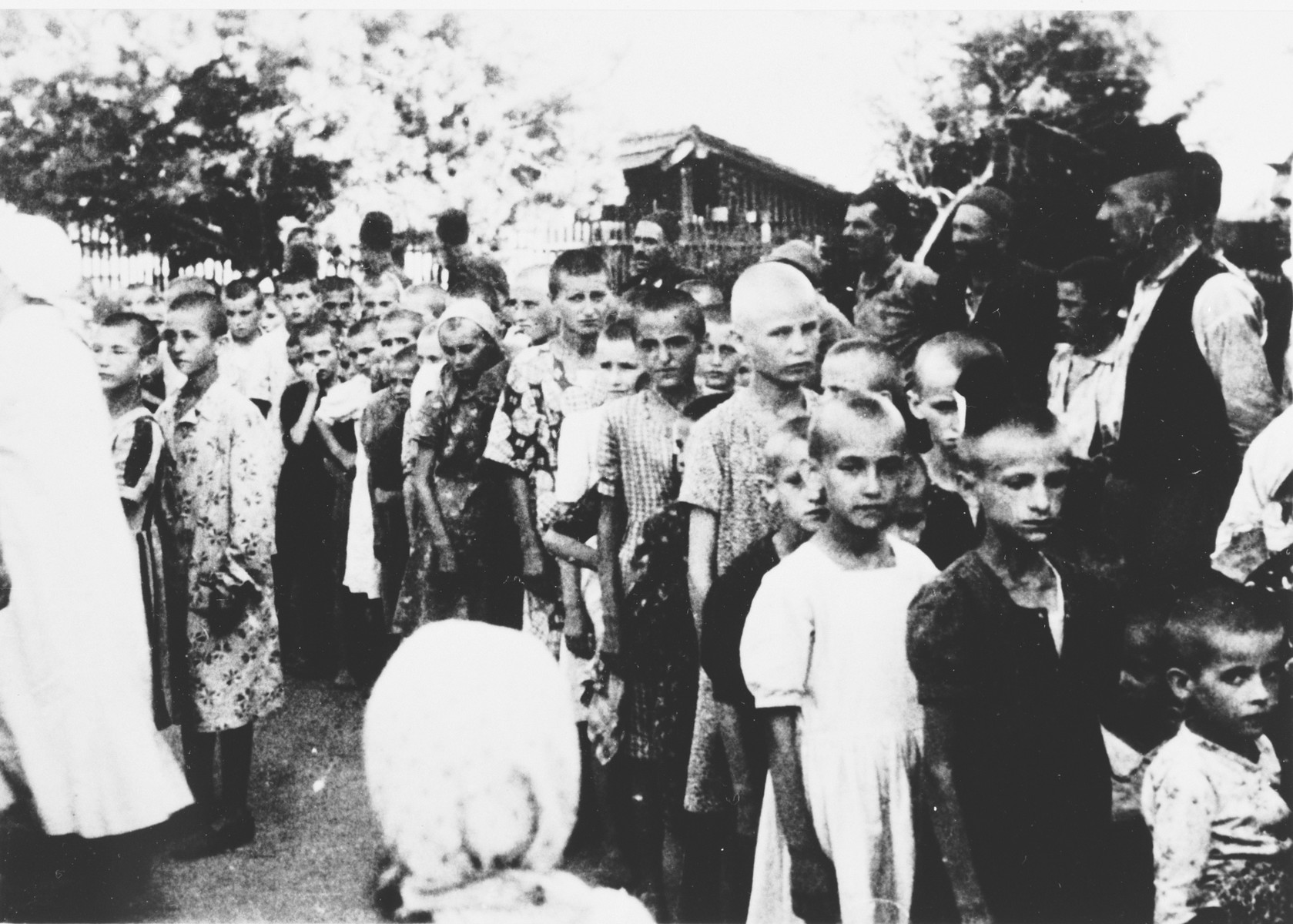 A group of children wait in line at an unidentified concentration camp [possibly Sisak] in Croatia.