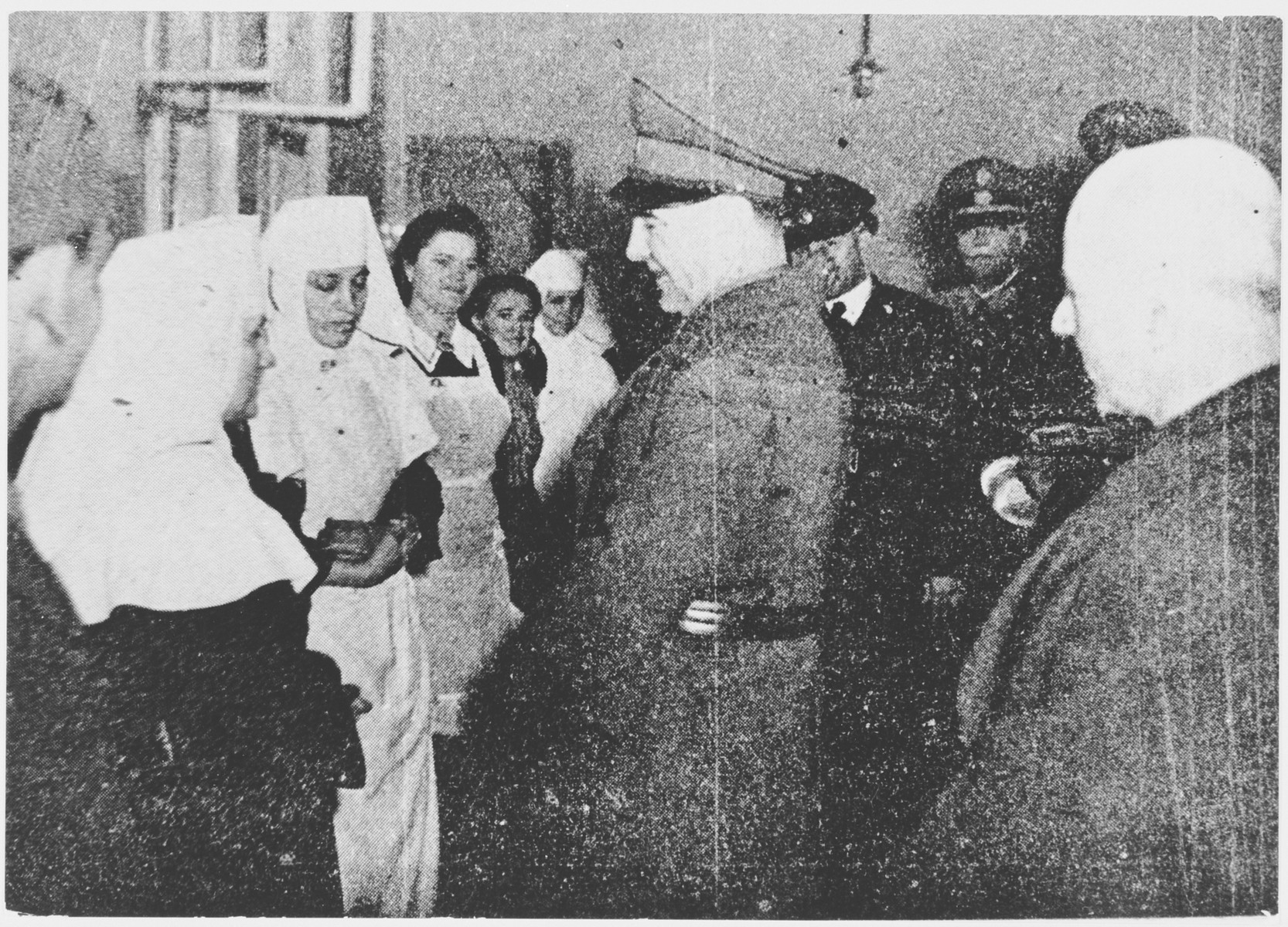 Croatian leader Ante Pavelic and Field Marshal Slavko Kvaternik talk to a group of nuns at an unidentified camp or institution.