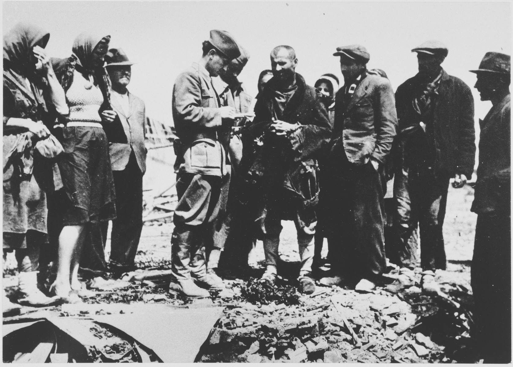 Members of the State Commission for the Investigation of Crimes Committed by the Occupiers and their Collaborators interview a group of men and women at the site ofthe Jasenovac III concentration camp.