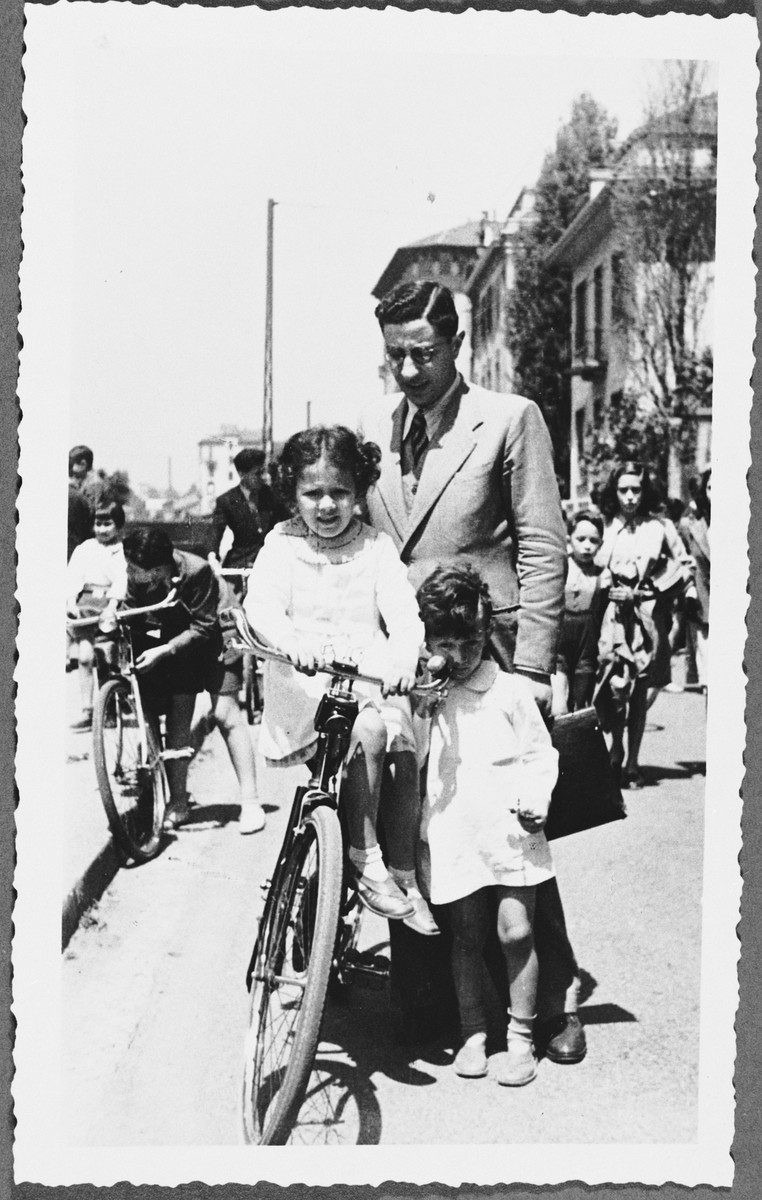 Rabbi Nathan Cassuto poses with his two older children, Susanna and David, next to a bicycle on a street in Milan.