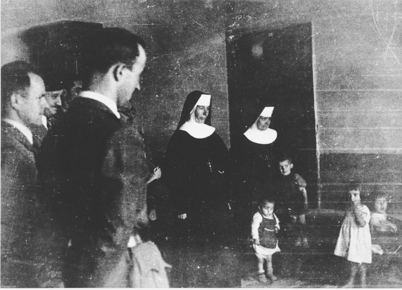 Croatian officials and Ustasa militia view a group of children in the care of nuns at the Jastrebarsko concentration camp.