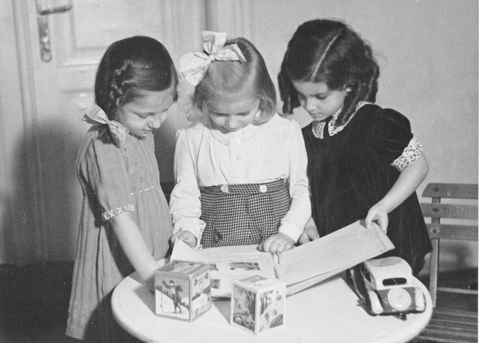 Three Jewish preschool girls look at a picture book in a playroom.  Pictured from left to right are: Judit Schichtanz, Marika Tusak and Susi Lieber.