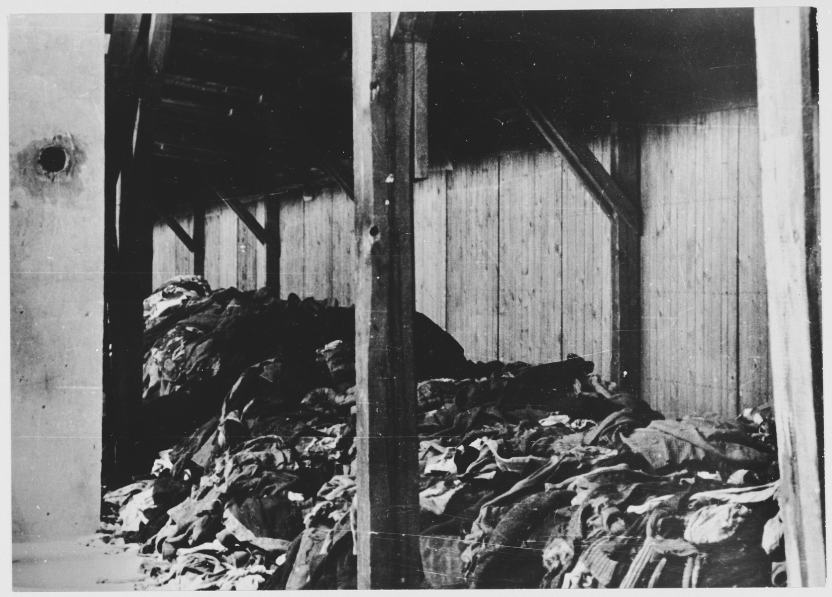 View of piles of clothing and other remains outside a barracks in the brickyard of Jasenovac III, known as KRPARA.  The photograph was taken during the May 1945 inspection of Jasenovac by the State Commission for the Investigation of Crimes Committed by the Occupiers and their Collaborators.