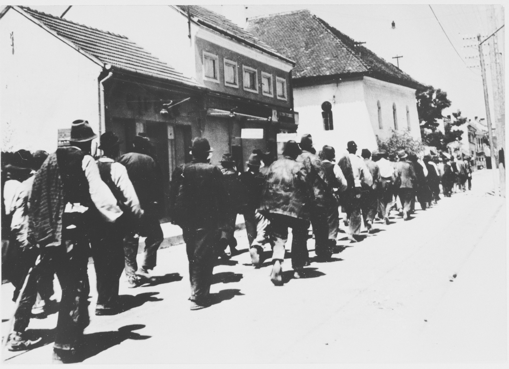 Serbian villagers from the Kozara region who have been rounded-up for deportation, march in a column through the streets of Prijedor.
