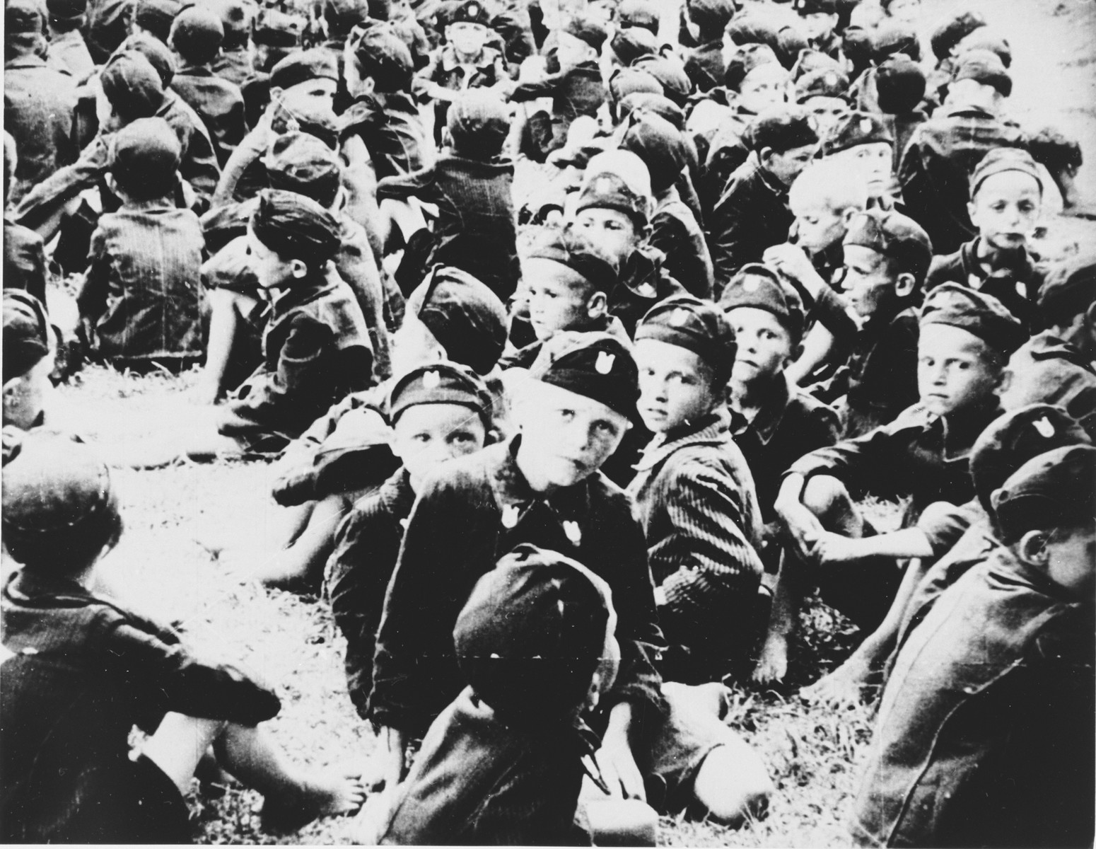 A large group of young Serbian children from the Kozara region who are dressed in Ustasa uniform, are assembled at the Stara Gradiska concentration camp.  The children were called Lubruric's Little Serbs after Maks Lubruric, the commandant of the Jasenovac concentration camp.  Dressing the imprisoned children in Ustasa uniforms was part of the Croatian regime's effort to reeducate the Serbian boys from the Kozara region.