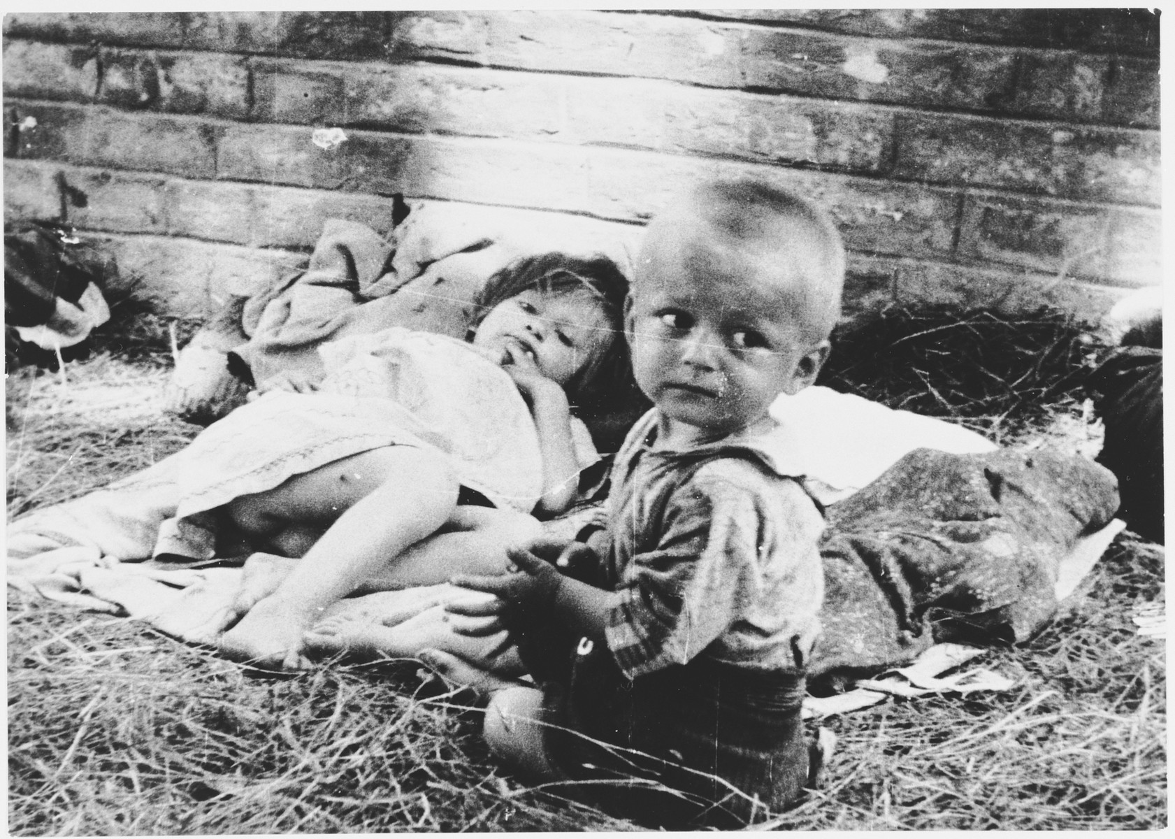 Two young children rest on a layer of straw on the floor of a barracks in the Sisak concentration camp.