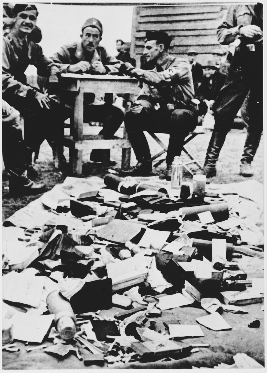 Ustasa personnel at the Jasenovac concentration camp view a pile of confiscated property looted from prisoners interned in the camp.