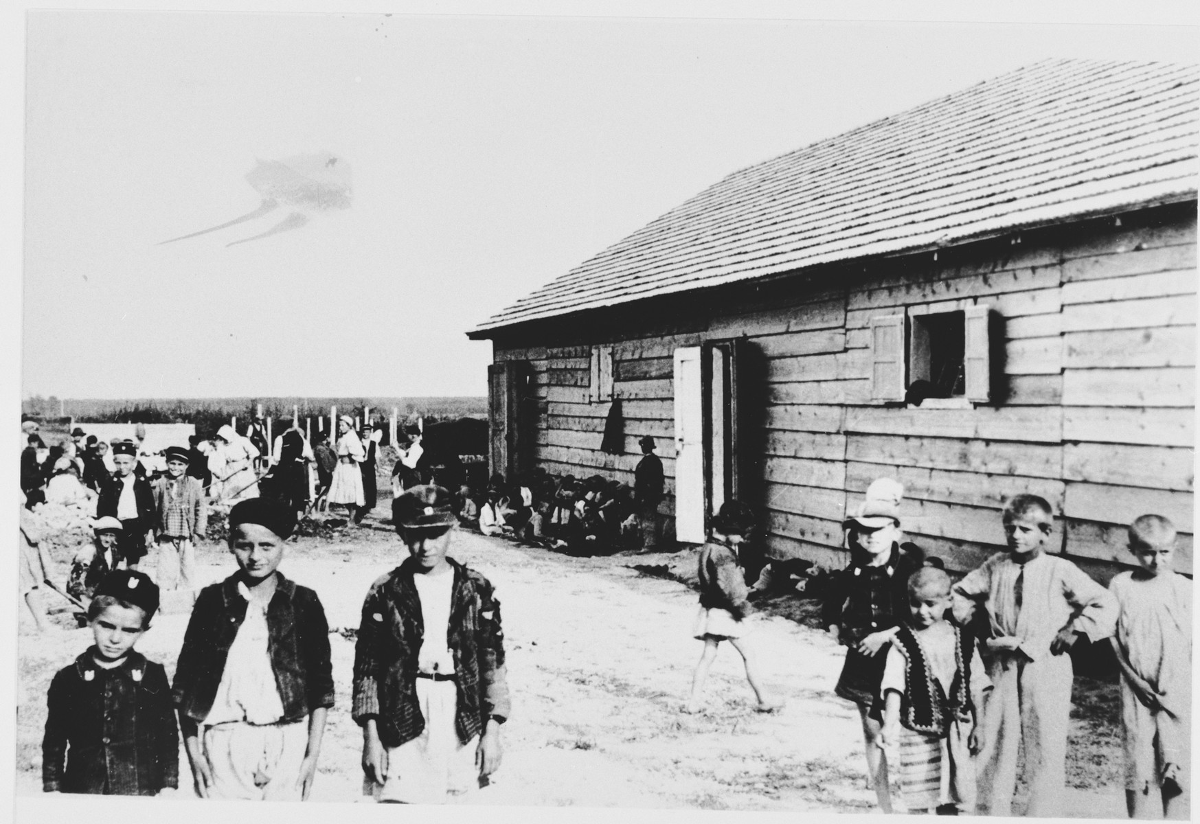 Children, some of whom are dressed in Ustasa uniforms, stand outside a barracks in the Gornja Rijeka concentration camp.