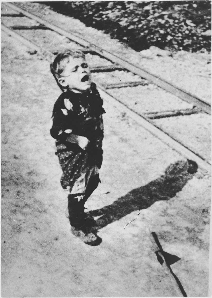 A little boy standing next to a train track cries out for help.