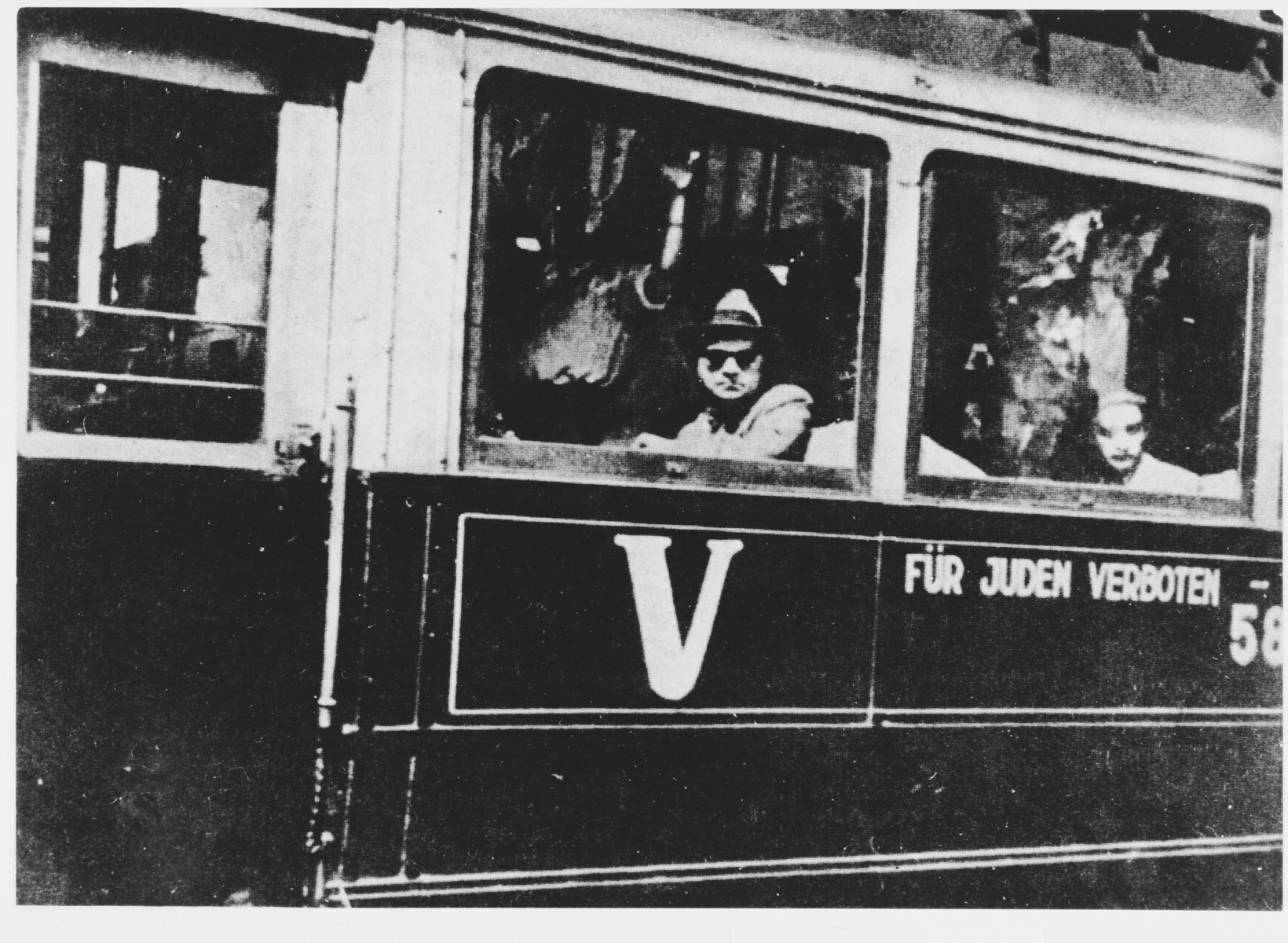 "Civilians ride a streetcar in Belgrade that is marked ""Fuer Juden Verboten"" (Forbidden to Jews)."