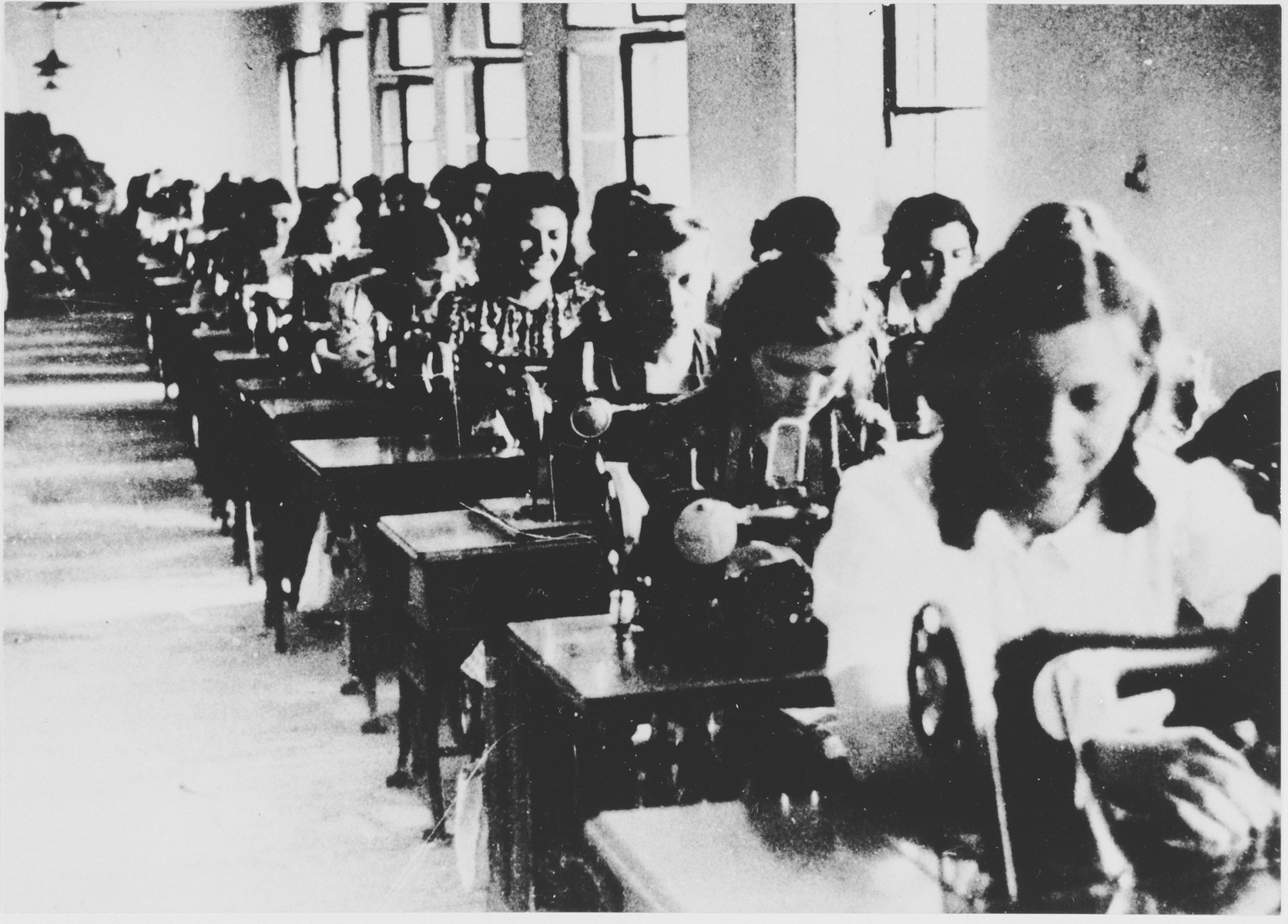 Female prisoners labor in a sewing workshop in the Jasenovac III concentration camp.  This photograph was used for propagandistic purposes by the Ustasa.