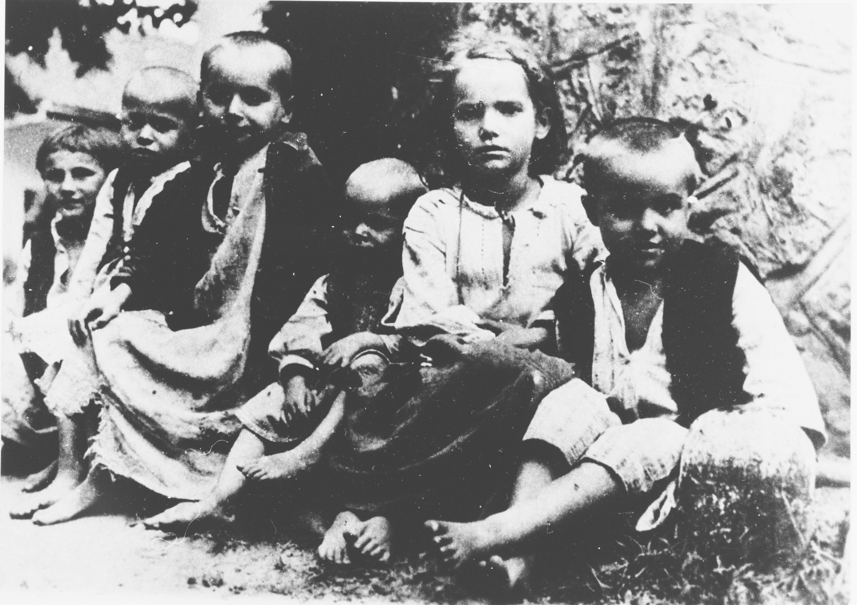 A group of barefoot, emaciated children sit outside at the Jastrebarsko concentration camp.
